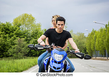 Man and woman riding motorcycle - Handsome young man riding...