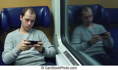Man playing game in his smartphone in a train. 4K video -...