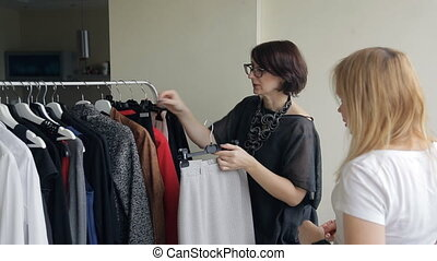 Two women are standing, and choose different clothes from the hanger.