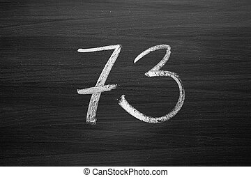 number seventy three enumeration written with a chalk on the...