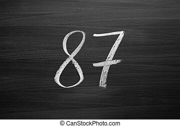 number eighty seven enumeration written with a chalk on the...