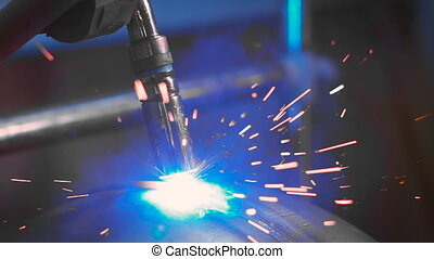 Bright sparks fly during the work of welding machine on...