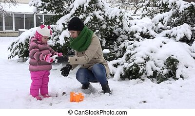happy woman with girl daughter play with first winter snow. Snowflakes fall
