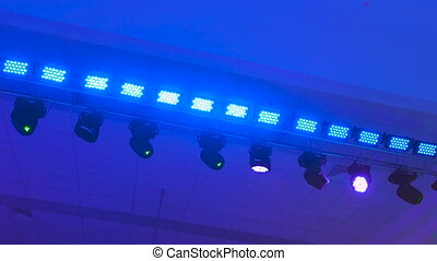 Concert lighting equipment in work. Professional lighting projectors automatically rotated and shining of different colors. Rays from the light equipment get into the camera lens.