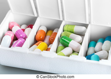 medical container with the various pills in different colors