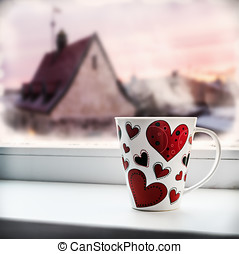 cup with heart on the window sill