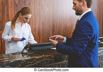 Mature man standing at check-in desk - Instantly connected...