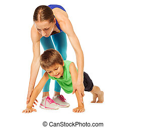Sporty mother helping her son doing pushing ups