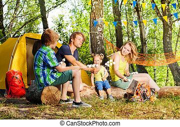 Happy family roasting marshmallow over campfire - Happy...