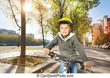 Kid boy in safety helmet riding bike on cycle path