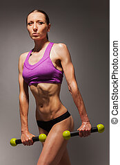 Portrait of fit young woman with dumbbells