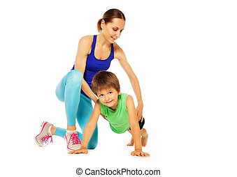Sporty mother teaching her son doing pushing ups