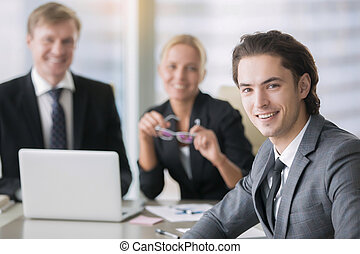 Group of business people and a smiling young man - Group of...