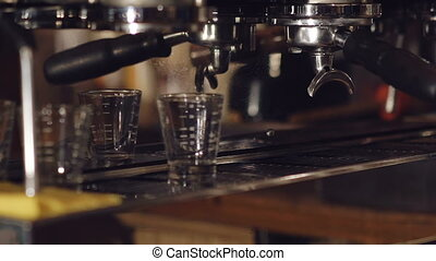 Two cups of espresso being poured from a professional espresso machine