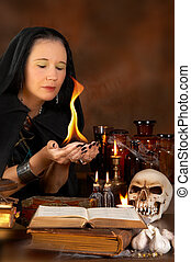 Bewitched fire - Halloween sorceress holding a fire flame in...