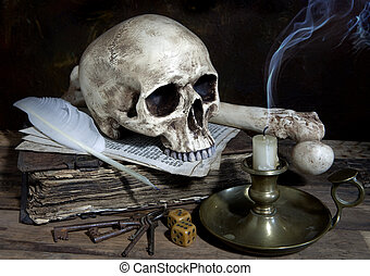 Blown out candle with skull and quill on antique book