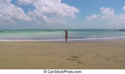 Slim girl standing on the sea cost with hands - Slim blonde...