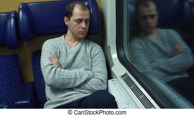 Tired man in sweater sleeping in his seat in a train. 4K...