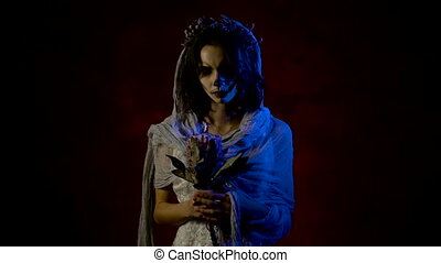 Close up of a ghost of young girl standing with the flowers in her hands and moving her arm inviting to follow her. Phantom of a mystical woman is having art creative Halloween make-up on her face. Dead girl is standing in the dark room against red background dressed in white wedding dress and looking at the camera.
