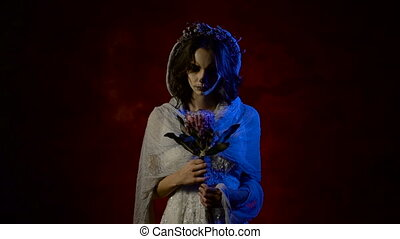 Close up of a ghost of young girl standing and spinning flower in her hands and moving her arm inviting to follow her. Phantom of a mystical woman having creative Halloween skull make-up. Dead girl is standing in the dark room against red background with her head covered with veil and flowers and looking at the camera.