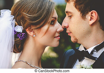 Bride looks with love at groom touching each other noses