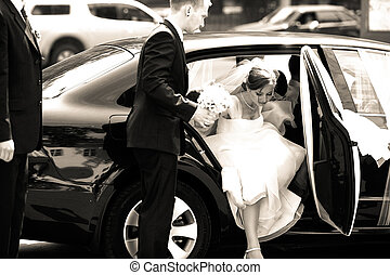Groomsman helps bride to step out of the car