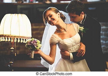 Bride reaches out a hand with a bouquet while groom hugs her...