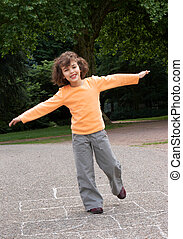 Hopping - Little girl playing hopscotch in the local park