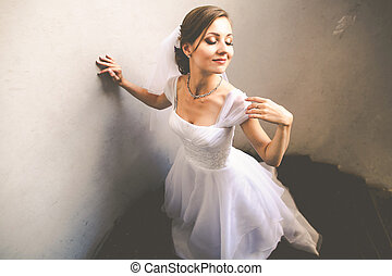 Bride touches her shoulder delicately standing with closed...