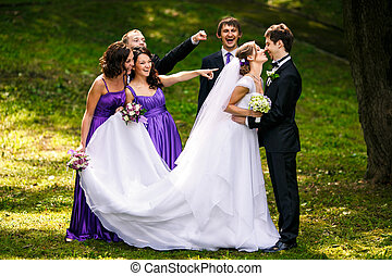 Friends reach out their fingers at newlyweds while they kiss