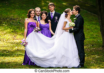 Newlyweds kiss standing behind her friends somewhere in the park