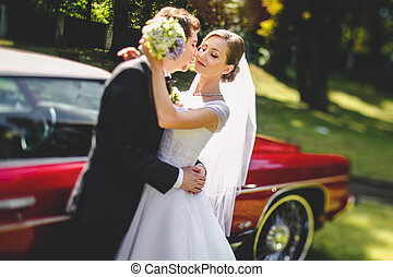 Bride daydreams in the hands of fiance standing behind an old red car
