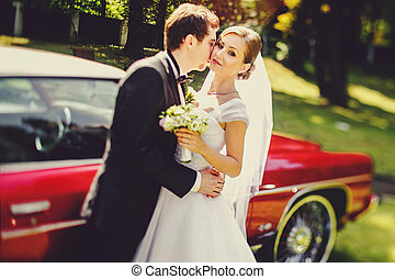 Bride looks serious being kissed by a groom behind old American car