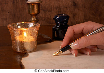 Parchment and pen - Hand writing on parchment with a golden...