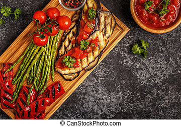 Grilled vegetables with tomato sauce and fresh herbs. -...