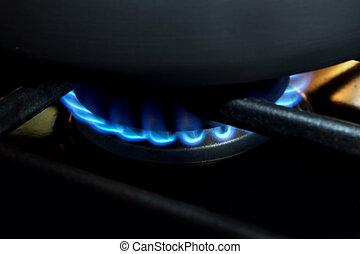 gas burner - one lit gas burner on a stovetop with blue...