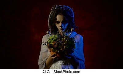 Close up of a ghost of young bride is standing with bunch of flowers in her hands. Mystical woman with art skull make-up on her face is staring at the camera and at the bunch.