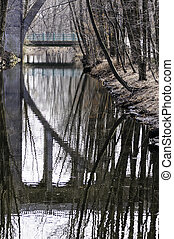 Bridge arch reflection in old canal paralleling Blackstone...