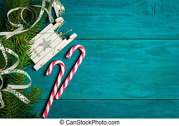 Christmas candy canes, toy sledge and branches of spruce -...