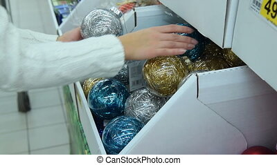 Woman buying Christmas balls in the store - Woman taking...