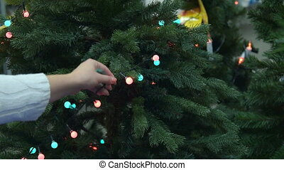 Christmas lights on the tree in the store - Woman looking at...