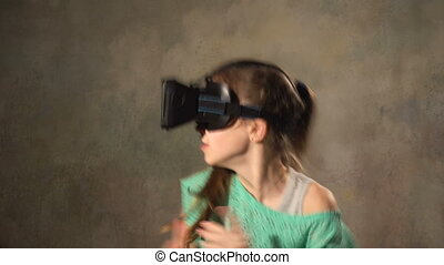 Teen young girl with VR headset. Playing and shooting in 3d...