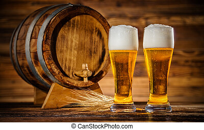 Glasses of lager with old wooden keg - Two glasses of lager...