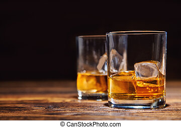 Glasses of whiskey with ice cubes served on wood - Two...