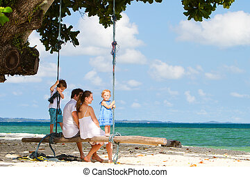 Family swinging on tropical beach - Young beautiful family...