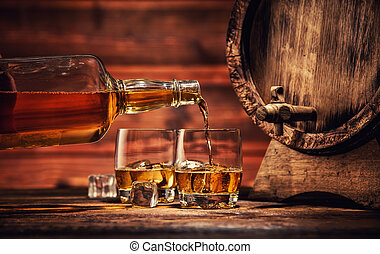 Glasses of whiskey with ice cubes served on wood - Pouring...