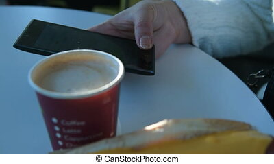 Woman using cellphone in fast food restaurant - Close-up...