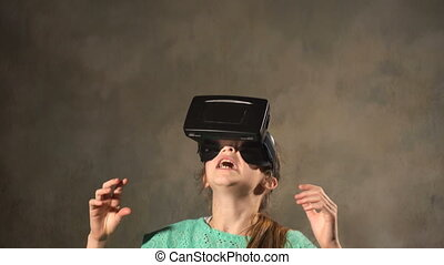 Teen young girl with VR headset. Playing in 3d virtual...