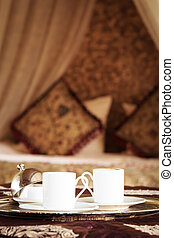 Two turkish coffee cups with oriental canopy bed at the...
