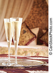Two champagne glasses with oriental canopy bed at the...